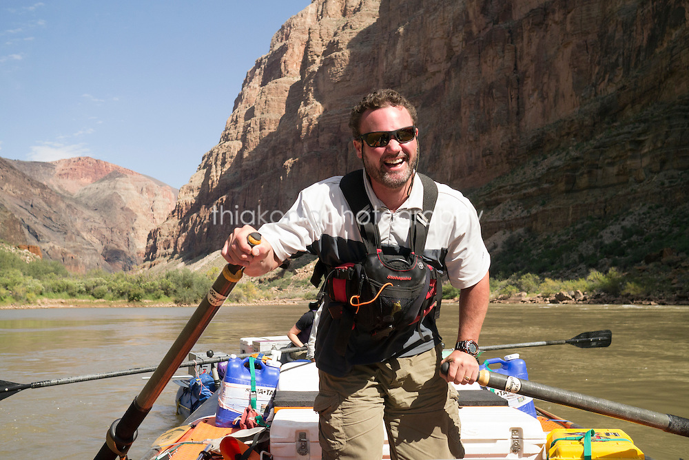 Boatman stands up to row on Colorado River, Grand Canyon, AZ