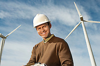 Engineer near wind turbines at wind farm, portrait