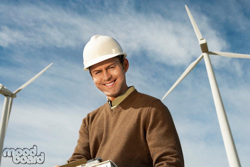 Engineer near wind turbines at wind farm, portrait