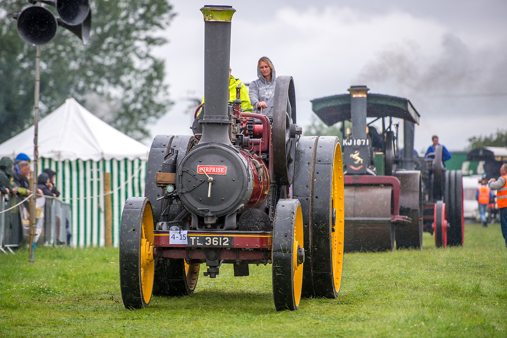 Young female helps operates vintage steam engine tractor as it rides along in parade, Masham, North Yorkshire, UK