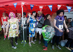 © licensed to London News Pictures. 18/06/2011. London, UK.  Racers shelter from a heavy down poor of rain before the race. Hundreds of men dressed as women take part in The Great Drag Race at Highbury Fields, North London today (18/06/2011). The 10k run is held to raise money for charity and increase the public's awareness of prostate cancer. Photo credit should read Ben Cawthra/LNP