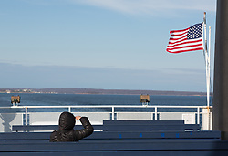 person on a Ferry boat in Winter saluting the American Flag