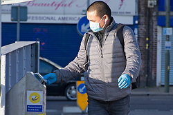 ©Licensed to London News Pictures 13/03/2020<br /> Pettswood, UK. A commuter wearing a face mask and latex gloves. London commuters at Pettswood train station this morning in Pettswood, Kent are keeping their distance from each other by standing a meter apart as the Coronavirus threat continues in the UK. Commuter numbers are down as many work from home.  Photo credit: Grant Falvey/LNP