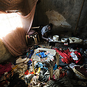 Moses (32), pictured in the room where he lives above his brother's home in Koidu in eastern Sierra Leone, suffers from schizophrenia. Moses says the year is 2003, which according to his brother is the year he fell ill. Though there does not appear to be a specific incident that triggered his illness, Moses says he hears planes and helicopters, possibly sounds from the fighting that raged around his home during the civil war that ended the year before he became unwell.