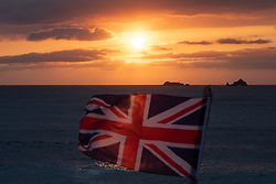 ©2020 Tom Nicholson. 10/05/2020. Padstow, UK. The sun sets behind a Union Jack flag on Constantine Bay beach, Cornwall, on the evening British Prime Minister Boris Johnson announced a 'road map' to begin the end of lockdown due after Covid-19, (Coronavirus). Photo credit : Tom Nicholson