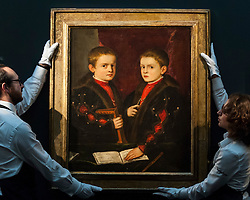 """© Licensed to London News Pictures. 02/12/2016. London, UK. Technicians show """"Portrait of two boys, said to be Members of the Pesaro Family"""" by Tiziano Vecellio, called Titian, (est. GBP 1-1.5m), at a preview of Sotheby's upcoming Old Masters Evening Sale in New Bond Street. Photo credit : Stephen Chung/LNP"""
