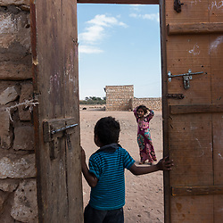 Dec. 25, 2014 - Socotra, Yemen. Children stand in a doorway in Neet on the southern coast of the island. The houses are traditionally built with a big family court yard. Male guests will generally enter by a side door to a dedicated room for men. The family area is only accessible to family members and women. © Nicolas Axelrod / Ruom