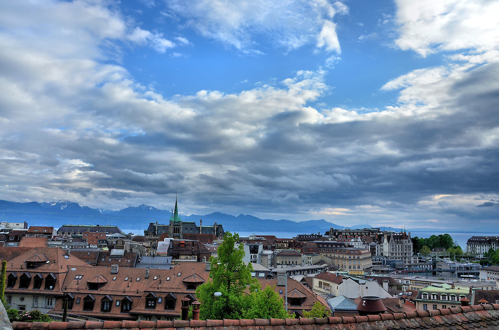 View of Lausanne from Notre Dame Cathedral in Switzerland <br /> During medieval times, someone would climb the stairs of the Cathedral of Notre Dame every night to watch over the city of Lausanne, Switzerland, for approaching invaders or fires.  The tradition of shouting out the all clear phrase &ldquo;c&rsquo;est le guet; il a sonn&egrave; l&rsquo;heure&rdquo; is still conducted hourly from 10:00 p.m. until 2:00 a.m. each night.  This is their view.  In the background are Lake Geneva and the Chablais mountain which is part of the Swiss Alps.