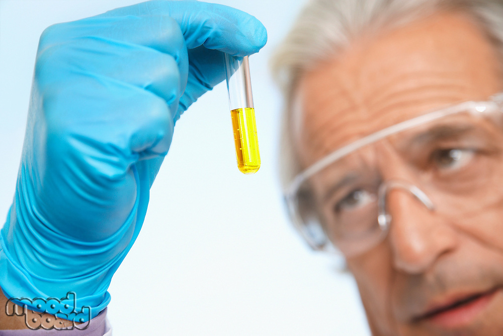 Scientist examining test tube of yellow liquid close-up focus on hand