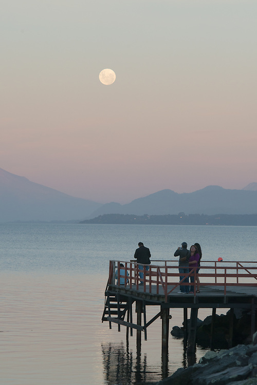 Tourists on Dock watching Moon, Puerto Varas, Chile  with Osorno Volcano and Llanquihue Lake