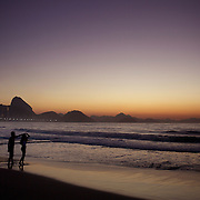 A couple dance and enjoy a tender moment as they witness the amazing sunrise at Rio de Janeiro's most famous beach Copacabana with Sugar Loaf mountain in the distance. Rio de Janeiro, Brazil. 21st July 2010. Photo Tim Clayton..