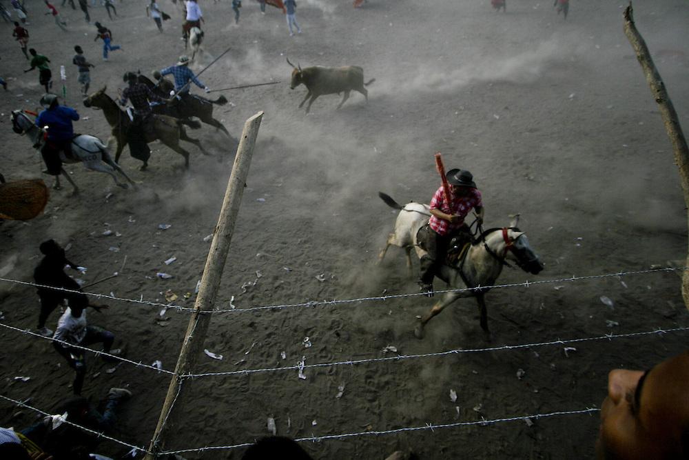Aficionados asisten a una corraleja mientras toreros y garrocheros corretean al toroen Arenal, Bolivar, Colombia