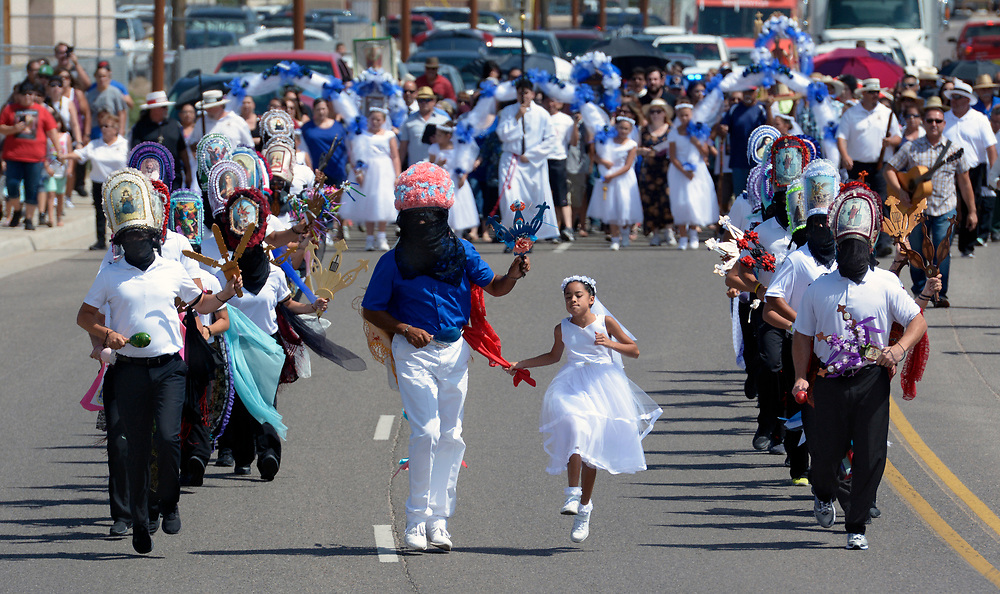 gbs081017c/RIO-WEST -- Edward Torres, a Monarca, center left, and Anna Carrilo a Malinches, center right, skip as they dance with Los Matachines in procession on South Camino del Pueblo from Our Lady of Sorrows Catholic Church during Las Fiestas de San Lorenzo on Thursday, August 10, 2017.(Greg Sorber/Albuquerque Journal)