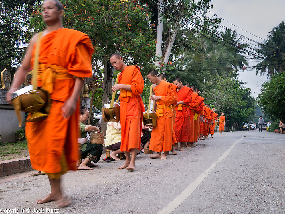 "11 MARCH 2013 - LUANG PRABANG, LAOS:  Buddhist monks collect alms during the tak bat in Luang Prabang. The ""Tak Bat"" is a daily ritual in most of Laos (and other Theravada Buddhist countries like Thailand and Cambodia). Monks leave their temples at dawn and walk silently through the streets and people put rice and other foodstuffs into their alms bowls. Luang Prabang, in northern Laos, is particularly well known for the morning ""tak bat"" because of the large number temples and monks in the city. Most mornings hundreds of monks go out to collect alms from people.   PHOTO BY JACK KURTZ"