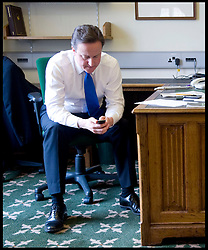 David Cameron Texting on his mobile phone in his office in Norman Shaw South, as he waits for news with members of his staff as they watch Gordon Brown resign as Prime Minister, Tuesday May 11, 2010,  Photo By Andrew Parsons / i-Images
