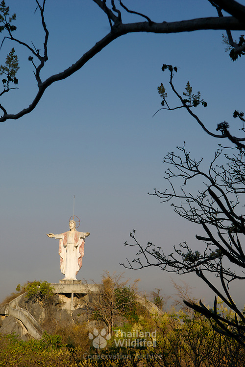 A Christ the redeemer statue nestled on top of a mountain at Wat Khao Tham Talu in Ratchaburi province, Thailand