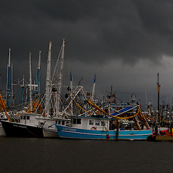 A storm band from Hurricane Alex moves in as Shrimp boat skimmers seek safe harbor due to heavy seas in Port Fourchon, Louisiana, U.S., on Wednesday, June 30, 2010. The BP Plc oil spill, which began when the leased Transocean Deepwater Horizon oil rig exploded on April 20, is gushing as much as 60,000 barrels of oil a day into the Gulf of Mexico, the government said. Photographer: Derick E. Hingle/Bloomberg