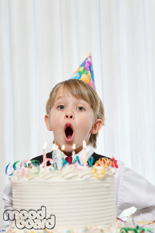 Portrait of young boy wearing party hat blowing candles on birthday cake