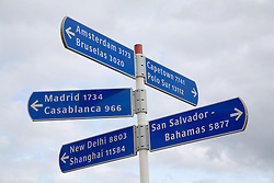 Humorous sign post listing distance to worldwide destinations,