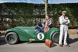 **CAPTION CORRECTION. Picture originally sent with wrong date. Picture was taken TODAY 11/09/2015** © licensed to London News Pictures. 11/09/2015<br /> Goodwood Revival Weekend, Goodwood, West Sussex. UK.<br /> The Goodwood Revival is the world's largest historic motor racing event. Competitors and enthusiasts dress in period fashions recreating the glorious days of the race circuit.<br /> Pictured. Driver and his family queue for the next race.<br /> <br /> Photo credit : Ian Whittaker/LNP