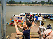 26 APRIL 2014 - CHAING SAEN, CHIANG RAI, THAILAND: Chinese tourists get on tourist boats in the Golden Triangle, a village in Chaing Saen district of Chiang Rai province, Thailand. The Golden Triangle is where Thailand, Myanmar (Burma) and Laos meet on the Mekong River. Chinese businesses play an increasingly important role in the Chiang Rai economy. Consumer goods made in China are shipped to Thailand while agricultural products made in Thailand are shipped to China. Large Chinese cargo boats ply the Mekong River as far south as Chiang Saen in the dry season and Chiang Khong when river levels go up in the rainy season.      PHOTO BY JACK KURTZ