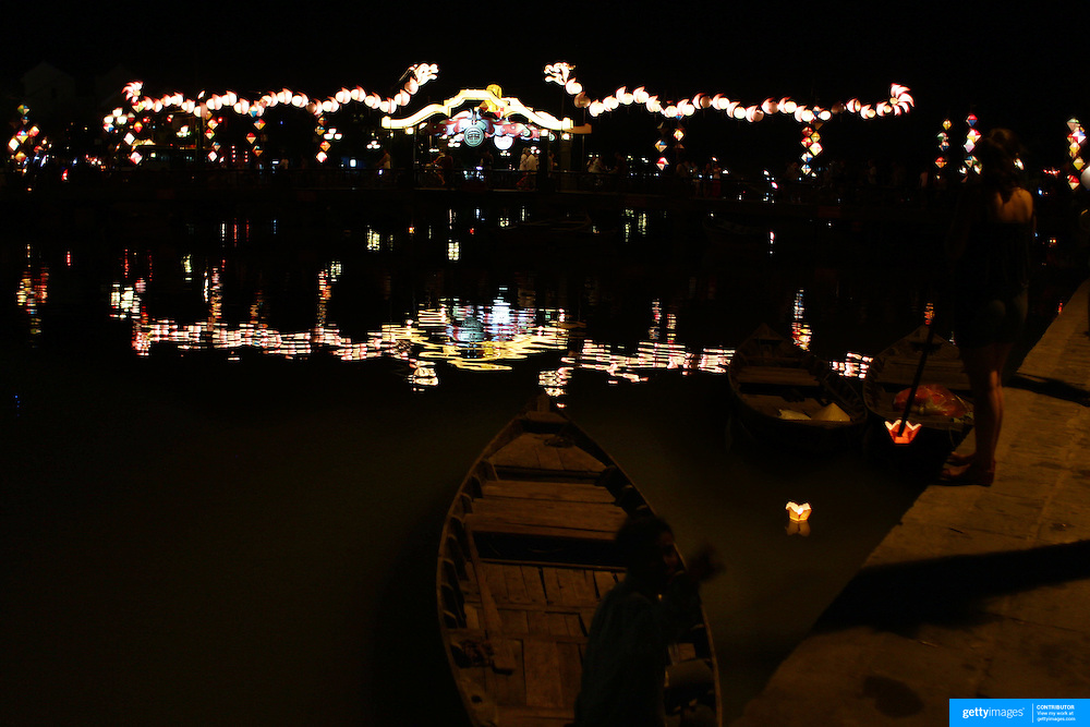 Floating candles sold to tourists, are launched down the Thu Bon River showing the lantern lit bridge at night time. Hoi An, Vietnam. Hoi An is an ancient town and an exceptionally well-preserved example of a South-East Asian trading port dating from the 15th century. Hoi An is now a major tourist attraction because of its history. Hoi An, Vietnam. 5th March 2012. Photo Tim Clayton
