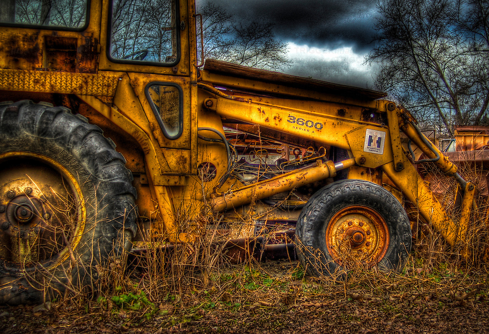 A yellow rusty digger in a field
