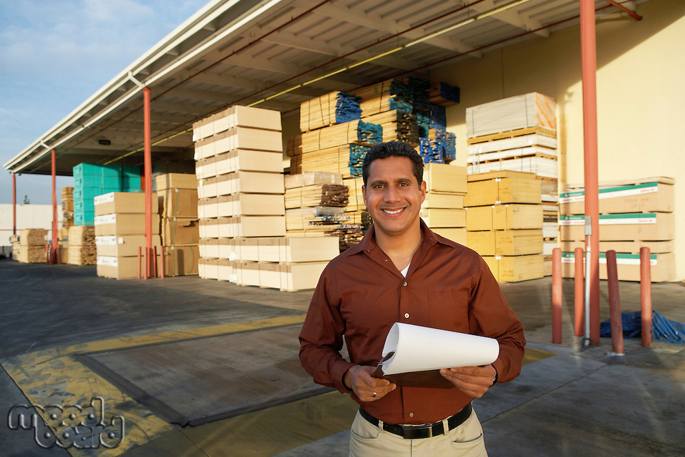Man with clipboard outside warehouse full of wood