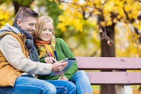 Portrait of attractive man showing digital tablet to his wife while sitting on bench in park