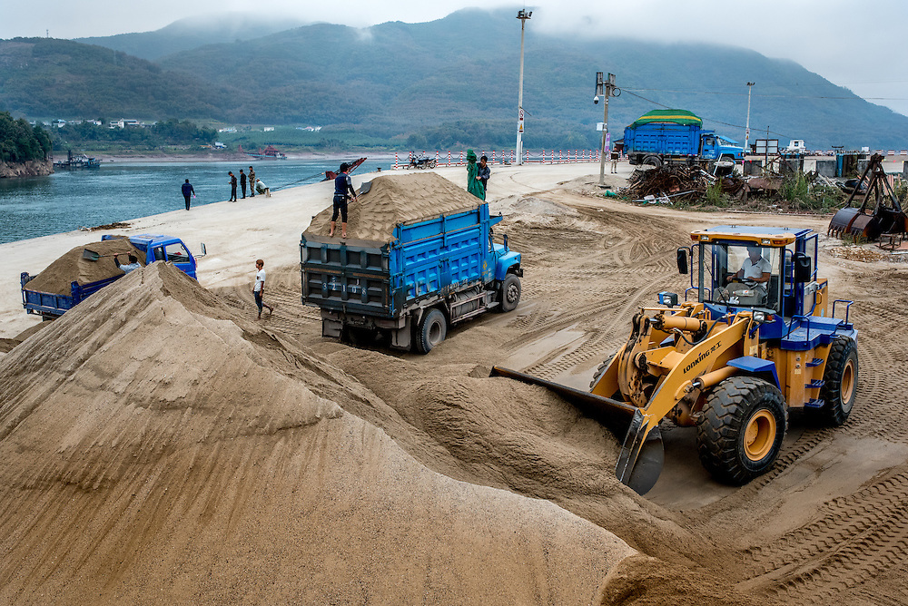 Trucks are loaded with dredged sand in the town of Simaogangzhen, Yunan, China. The dredged sand is sold locally and to large scale construction sites in nearby major cities such as Kunming and Jinhong.