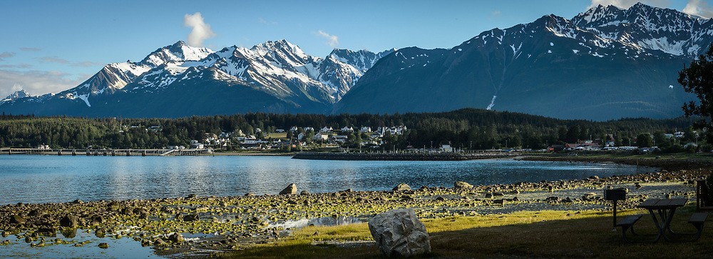 """Early evening sun basks on the town of Haines and the mountains of the Chilkat Range as seen from """"Picture Point"""" in southeast Alaska. In the center are the buildings of the former U.S. Army fort, Ft. William H. Seward."""