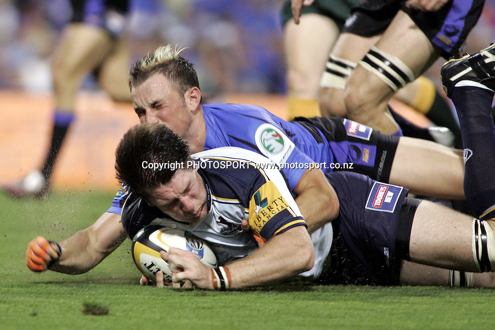 Ben White (flanker) of the Brumbies is brought down by Mat Henjak during the opening round of the 2006 Super 14 rugby union match between the Western Force and ACT Brumbies at Subiaco Oval, Perth, Western Australia, on Friday 10 February, 2006.  Final score was Western Force 10 - AC Brumbies 25.  Photo: Christian Sprogoe/PHOTOSPORT