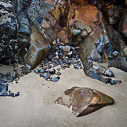 Multi-colored rocks lining the edge of the beach along the Oregon Coast.