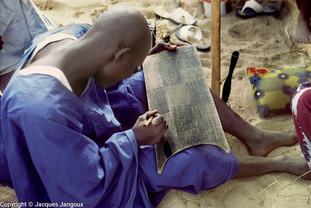 Africa, Sahel region, Chad, Islands of Lake Chad. Kanembu man studying the Quran (Koran), writing verses on a wooden Quranic teaching tablet. The tablet can be washed and written over again.