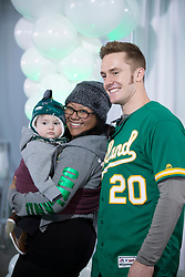 A's first baseman Mark Canha poses for a photo with Angela Silva of San Jose and her son Hunter, 9 months, during Oakland Athletics FanFest at Jack London Square on Saturday, Jan. 27, 2018 in Oakland, Calif. (D. Ross Cameron/SF Chronicle)
