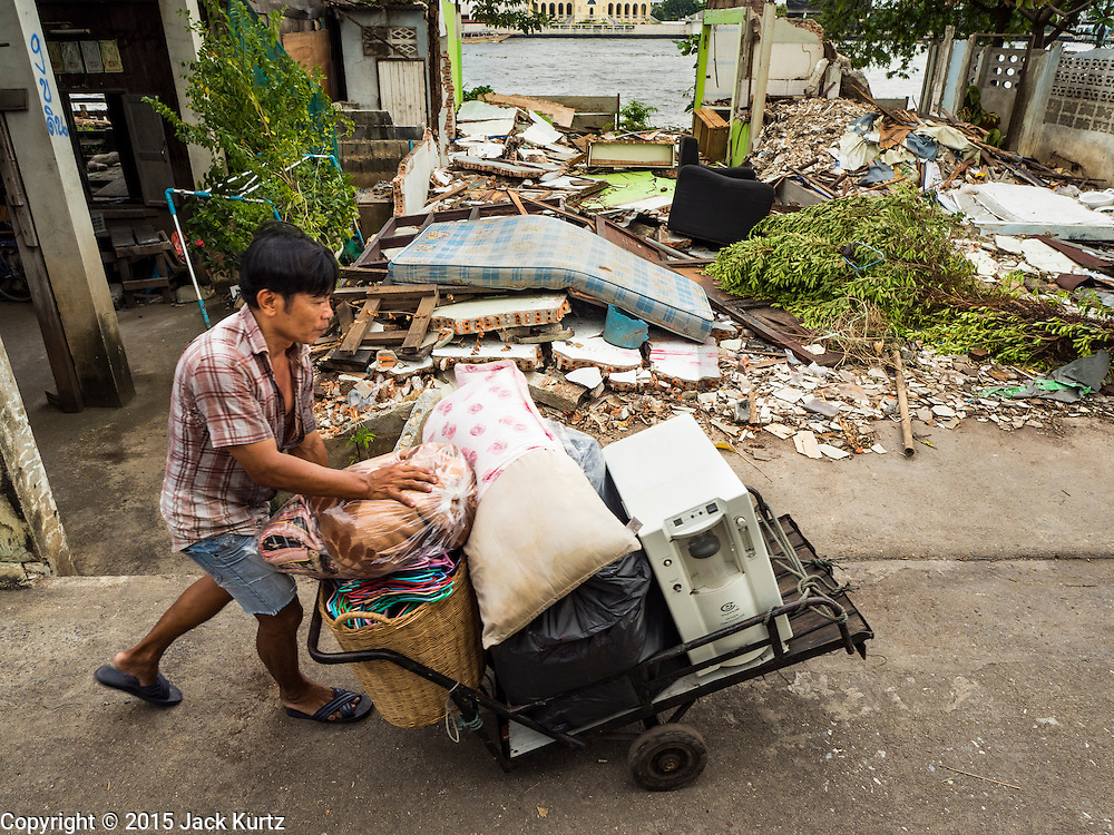 12 NOVEMBER 2015 - BANGKOK, THAILAND:   A man takes the belongings of a Wat Kalayanmit resident to a waiting truck on the day the family was being evicted. Fifty-four homes around Wat Kalayanamit, a historic Buddhist temple on the Chao Phraya River in the Thonburi section of Bangkok, are being razed and the residents evicted to make way for new development at the temple. The abbot of the temple said he was evicting the residents, who have lived on the temple grounds for generations, because their homes are unsafe and because he wants to improve the temple grounds. The evictions are a part of a Bangkok trend, especially along the Chao Phraya River and BTS light rail lines. Low income people are being evicted from their long time homes to make way for urban renewal.       PHOTO BY JACK KURTZ