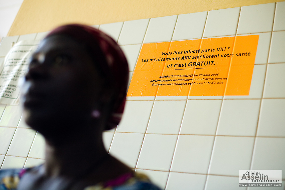 A woman sits by a sign advertising free ARV drugs at the NDA health center in Dimbokro, Cote d'Ivoire on Friday June 19, 2009.