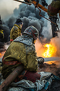 A firefighter sits on the ground as he pumps water into a flaming oil well on the outskirts of Qayyarah, set ablaze by retreating IS militants, on December 12, 2016.