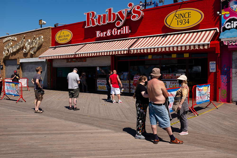 Brooklyn, NY - 14 June 2020. People wait to be served outside Ruby's Bar & Grill on the Coney Island boardwalk, keeping 6 feet of distance between them. A group of 3 people stands close together nearby.
