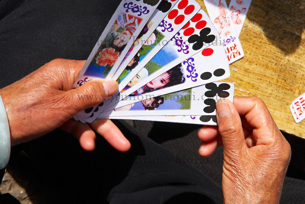 Chine. Province du Yunnan. Ville de Lijiang. Patrimoine mondial de l'UNESCO. Femme Naxi jouant aux cartes (jeux local). // China. Yunnan province. City of Lijiang. UNESCO World Heritage. Naxi womans playing cards (local game).