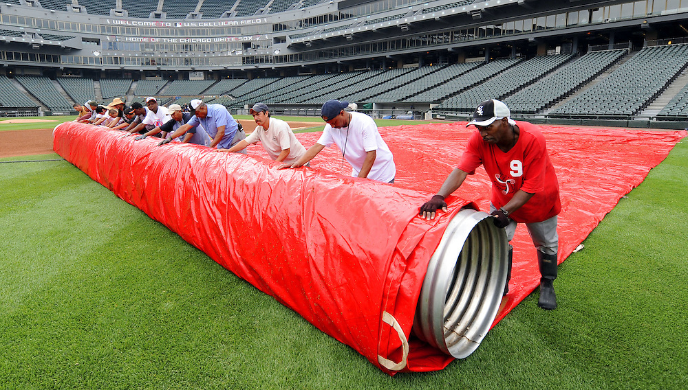 CHICAGO - JULY 19: The Chicago White Sox ground crew roll out the tarp at U.S. Cellular Field in Chicago, Illinois.
