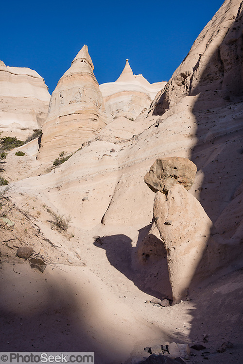 "Hoodoos. See fantastic hoodoos and a great slot canyon in Kasha-Katuwe Tent Rocks National Monument, in New Mexico, USA. Hike the easy Cave Loop Trail plus Slot Canyon Trail side trip (3 miles round trip), 40 miles southwest of Santa Fe, on the Pajarito Plateau. Distinctive cone-shaped caprocks protect soft pumice and tuff beneath. Geologically, the Tent Rocks are made of Peralta Tuff, formed from volcanic ash, pumice, and pyroclastic debris deposited over 1000 feet thick from the Jemez Volcanic Field, 7 million years ago. Kasha-Katuwe means ""white cliffs"" in the Pueblo language Keresan."