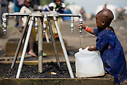 A young displaced child fills a jerican with water from a pipe at the Kibati IDP camp on the outskirts of Goma, Eastern Democratic Republic of Congo on Friday December 12, 2008