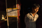 Ship worker in moment of thought in morning light, Yangon