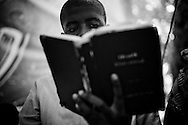 A boy reads a hymn book during Sunday church services at Eglise Baptiste Bellevue Salem MEBSH church in Port-au-Prince, Haiti.