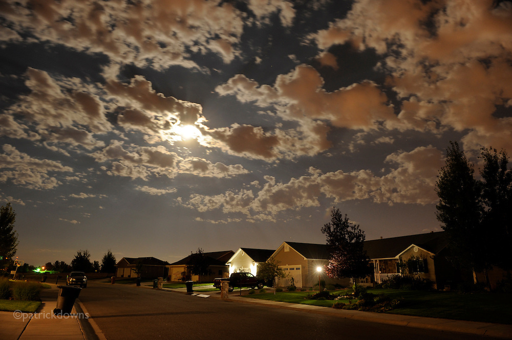 Night clouds move above a quiet street near midnight.