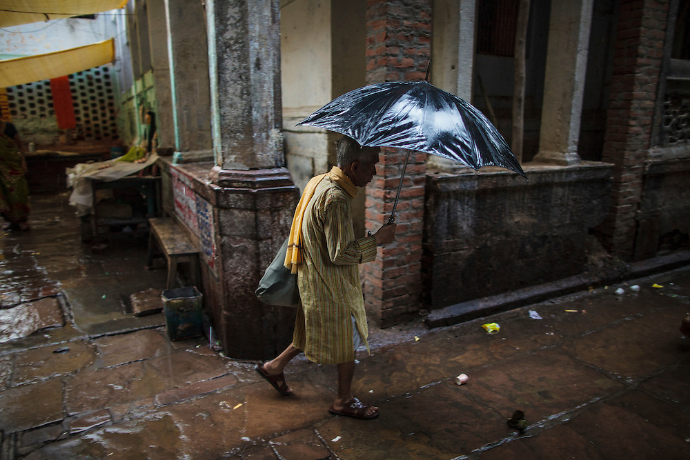 Man walking with an umbrella in the rain in an alley in Varanasi Old town, in India.