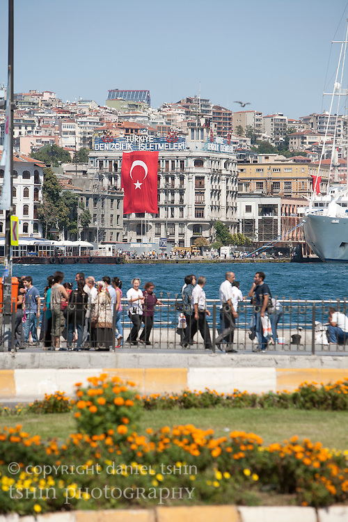 People walking along the Golden Horn of the Bosphorus on a clear sunny day with Karaköy in the background. A Turkish flag is draped on the side of a building in preparation for Victory Day in late August.