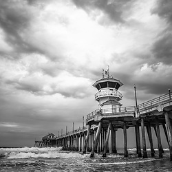 Photo of Huntington Beach Pier dramatic storm clouds in black and white. Huntington Beach is a popular Southern California beach city also known as Surf City USA.