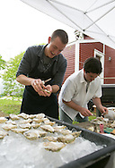 Cohasset, MA 05/11/2013.Chefs Evan Gaudreau, left, and Ben Murphy engage in a friendly oyster shucking competition at Holly Hill Farm on Saturday..Alex Jones / www.alexjonesphoto.com